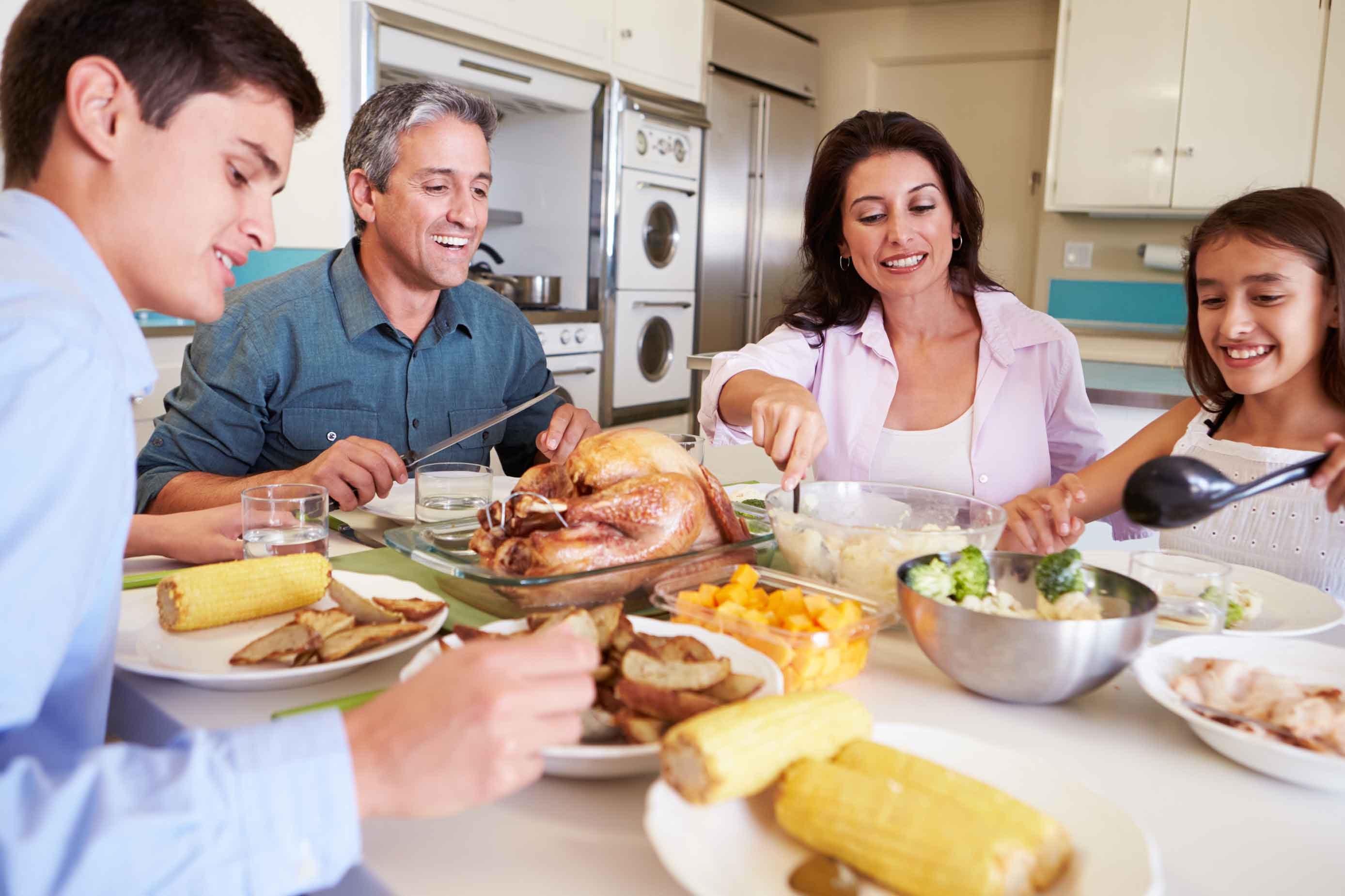 family of four eating turkey dinner at table